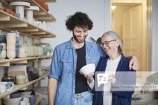 Smiling man and woman looking at bowl in pottery class