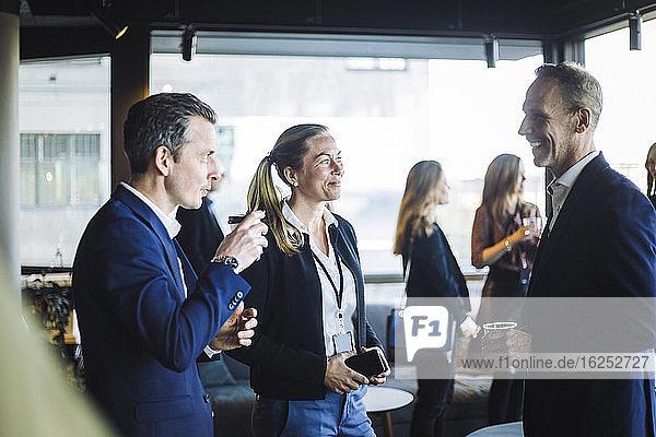 Männliche und weibliche Kollegen diskutieren im Stehen am Arbeitsplatz