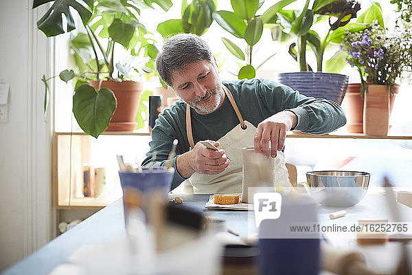 Mature man making craft product in pottery class