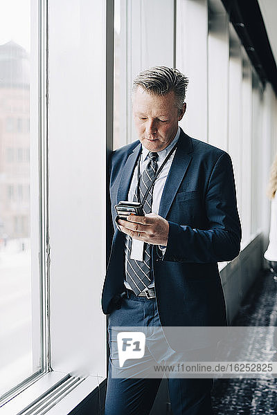 Entrepreneur using phone while standing by window in office