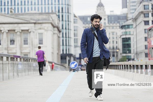 Geschäftsmann geht und spricht mit einem Smartphone auf der Stadtbrücke