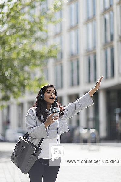 Frau mit Kopfhörern und Smartphone begrüßt Taxi in Menschenmenge