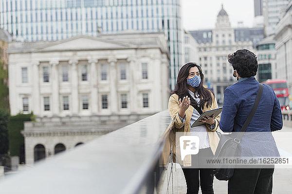 Geschäftsleute mit Gesichtsmasken im Gespräch auf der City Bridge  London  UK