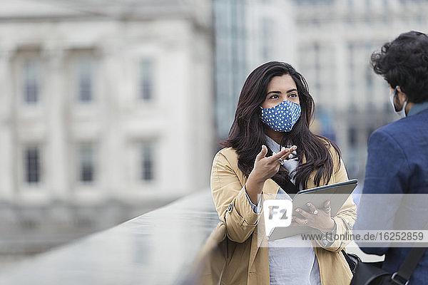 Geschäftsleute mit Gesichtsmasken mit digitalem Tablet  die im Freien sprechen