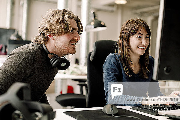 Male and female smiling professionals discussing while sitting in office