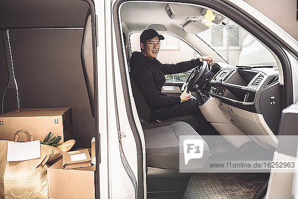 Portrait of smiling driver with package sitting in truck