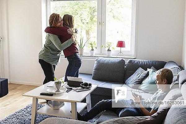 Lächelnde Mutter umarmt Tochter  während der Sohn zu Hause telefoniert