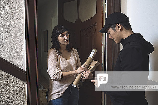 Female customer holding package while delivery man with phone standing at doorstep