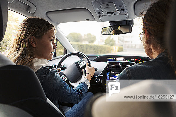 Teenage girl learning to drive from mother during weekend