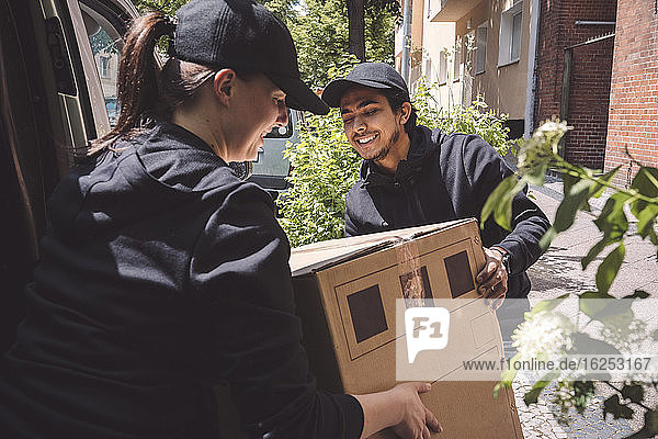 Smiling delivery colleagues holding cardboard box near truck