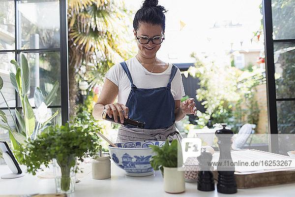 Lächelnde Frau kocht mit Balsamico-Essig in der Küche