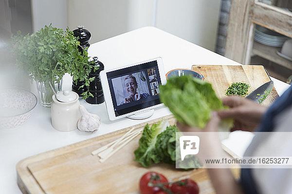 Frau beim Kochen und Video-Chat mit Freunden auf digitalem Tablet-Bildschirm