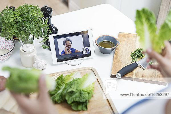 Frau beim Salatkochen und Video-Chat mit Freunden in der Küche