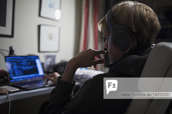 Teenager Junge mit Kopfhörern am Computer im dunklen Schlafzimmer