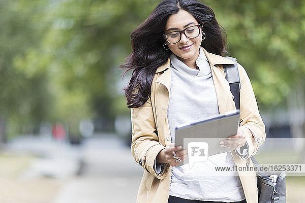 Geschäftsfrau mit digitalem Tablet geht im Park