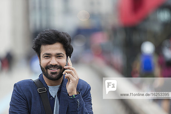Portrait smiling businessman talking on smart phone outdoors