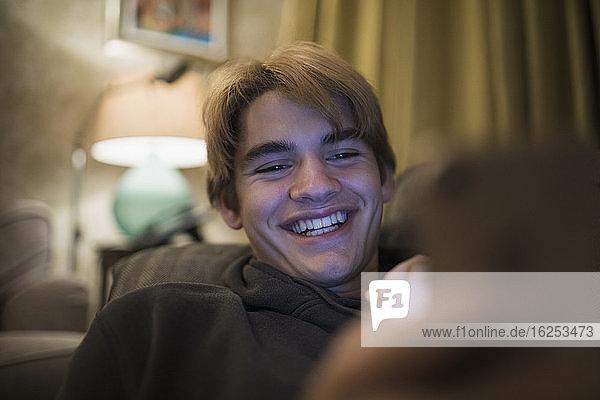 Nahaufnahme eines lächelnden Teenagers mit einem Smartphone