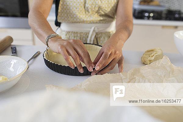 Frau backt und bereitet Kuchenkruste in der Küche vor