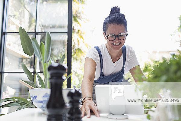 Lächelnde Frau mit digitalem Tablett am Esstisch