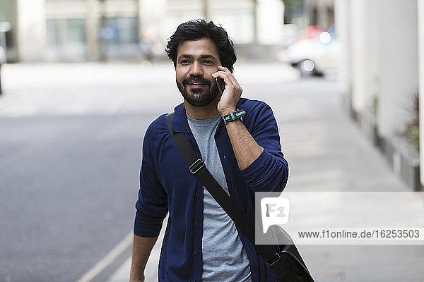 Mann mit Smartphone geht auf dem Bürgersteig