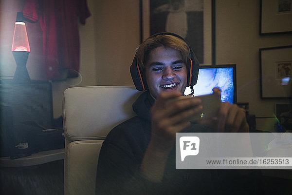 Lächelnder Teenager mit Kopfhörern und Smartphone im Schlafzimmer