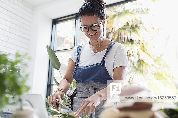 Smiling woman cutting fresh herbs in kitchen