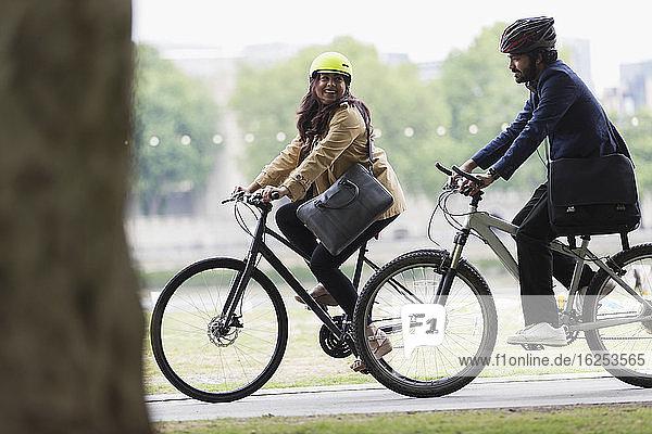 Glückliches Paar mit Helmen auf Fahrrädern im Park