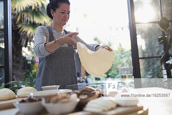 Frau dehnt Pizzateig in der Küche