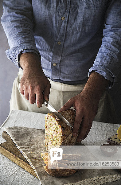 Mann schneidet frischen hausgemachten Sauerteigbrotlaib