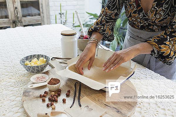 Frau backt am Küchentisch