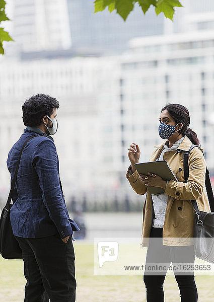 Geschäftsleute mit Gesichtsmasken reden im Stadtpark