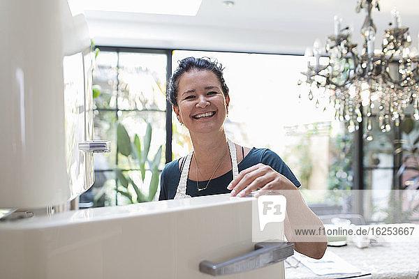 Porträt einer glücklichen Frau am offenen Kühlschrank in der Küche