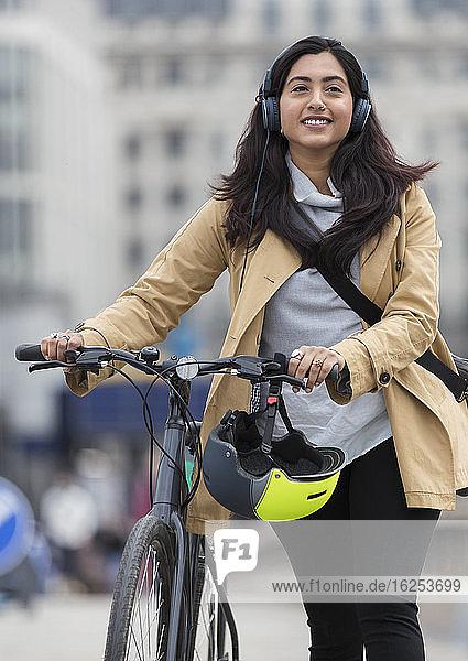 Lächelnde Frau mit Kopfhörern beim Fahrradfahren