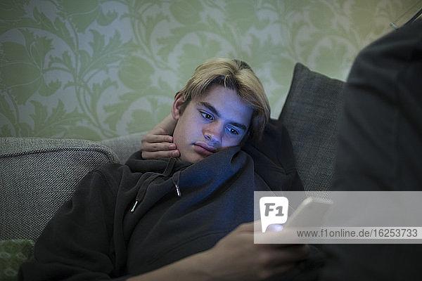 Teenager-Junge benutzt Smartphone auf Sofa
