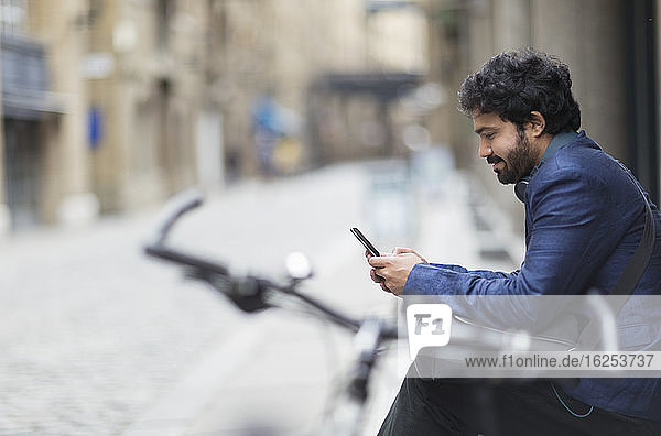 Businessman with bicycle using smart phone on city street