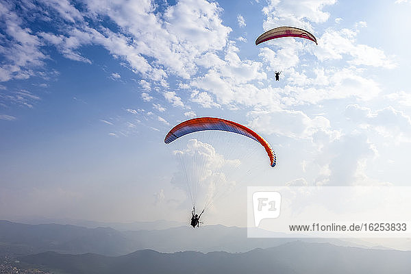 Paragliders flying high above the city of Pokhara  Nepal in the Himalayan mountains  on a sunny  smoggy day; Pokhara  Gandaki Pradesh  Nepal