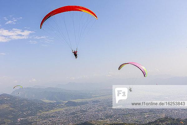 Gleitschirmflieger fliegen hoch über der Stadt Pokhara  Nepal im Himalaya-Gebirge  an einem sonnigen  verrauchten Tag; Pokhara  Gandaki Pradesh  Nepal