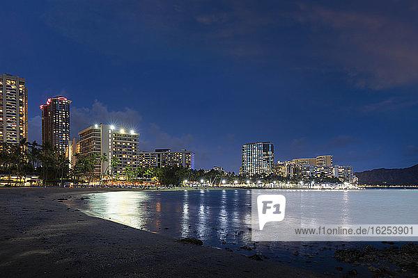 Waikiki bei Sonnenuntergang  mit beleuchteten Gebäuden und ruhiger Uferpromenade; Honolulu  Oahu  Hawaii  Vereinigte Staaten von Amerika