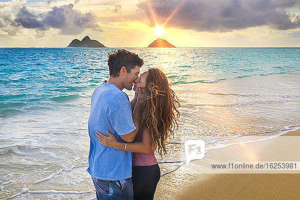 A couple stands kissing on Lanakai beach on the Hawaiian island of Oahu at sunset; Lanakai  Oahu  Hawaii  United States of America