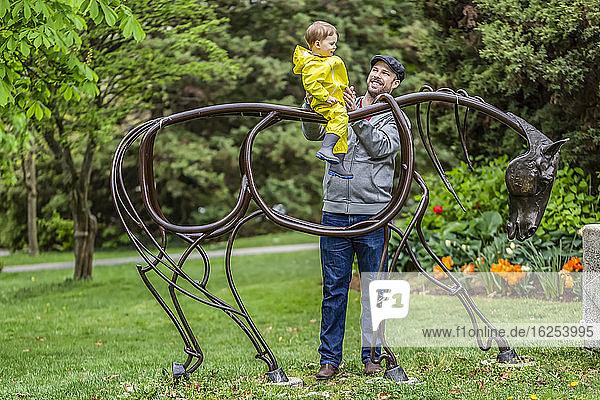 Vater hält die Tochter fest  die an einem bedeckten Frühlingstag auf einer Pferdeskulptur im Park sitzt; North Vancouver  British Columbia  Kanada