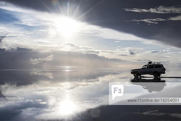 Allradantrieb und Reflexion während der Regenzeit (Dezember-Februar) im Salar de Uyuni  der größten Salzfläche der Welt; Abteilung Potosi  Bolivien
