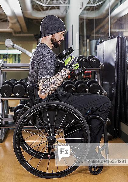 Ein querschnittsgelähmter Mann beim Training mit freien Gewichten vor einem Spiegel im Freizeitzentrum: Sherwood Park  Alberta  Kanada