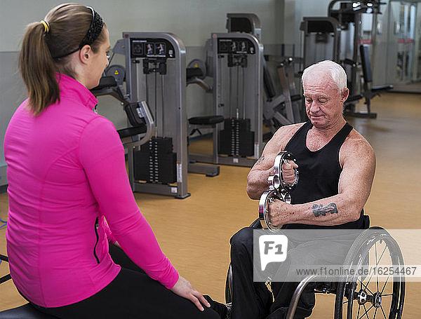 Ein älterer querschnittsgelähmter Mann trainiert mit Hilfe seines Trainers in einer Fitnesseinrichtung mit einem runden Handgerät; Sherwood Park  Alberta  Kanada