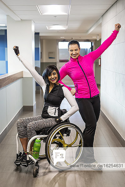 A paraplegic woman and her trainer do a celebratory pose for the camera while in a hallway in a recreational facility: Sherwood Park  Alberta  Canada