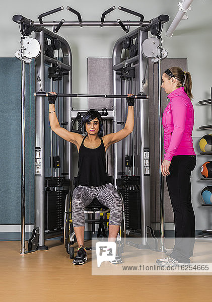 A paraplegic woman working out using a lat pull down machine with her personal trainer coaching her in a fitness facility; Sherwood Park  Alberta  Canada