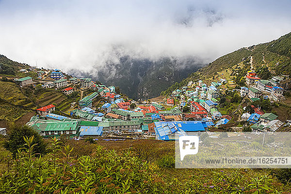 View looking down the mountain at the village of Namche Bazaar  a major stop and often used as a layover  along the Everest and Gokyo treks  to all the colourful teahouses  on a cloudy autumn morning  with clouds mostly obscuring the mountain across the valley; Namche Bazaar  Nepal