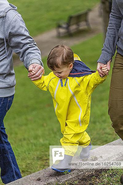 Nahaufnahme einer Mutter und eines Vaters  die mit ihrer kleinen Tochter Händchen halten  während sie im Park auf einem Betonvorsprung entlang läuft; Surrey  British Columbia  Kanada