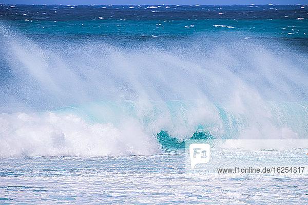 Plätschernde Wellen entlang der Küste mit einem strahlend blauen Himmel am Horizont  Banzai-Pipeline; Oahu  Hawaii  Vereinigte Staaten von Amerika