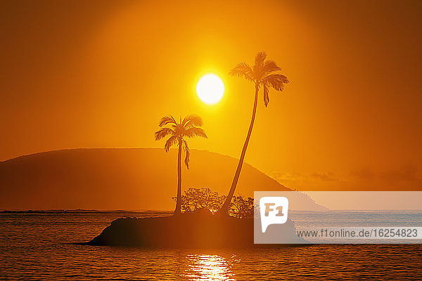 Sunrise at Kahala Beach  Wai?alae Beach Park  with a flare around the sun in a glowing red sky reflected in the tranquil water; Oahu  Hawaii  United States of America