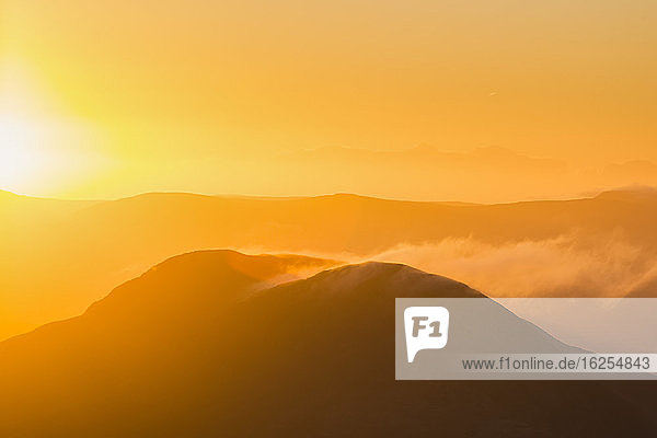 Silhouette of a hill in Kerry at sunrise with snow being blown off the top  MacGillycuddy's Reeks; County Kerry  Ireland